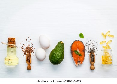 Selection food sources of omega 3 . Super food high omega 3 and unsaturated fats for healthy food. Olive oils ,salmon ,flax seeds ( linseed ) ,chia seeds ,eggs and avocado on white wooden background.