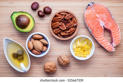 Selection food sources of omega 3 and unsaturated fats. Super food high vitamin e and dietary fiber for healthy food. Almond ,pecan ,hazelnuts,walnuts ,olive oil ,fish oil ,salmon  on cutting board.