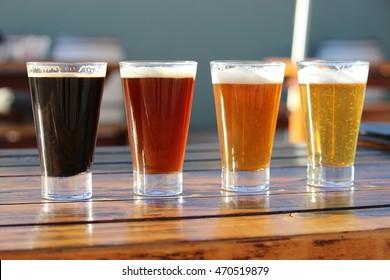 Une sélection de quatre bières artisanales lors d'une dégustation sur une table en bois