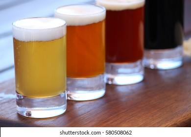 Une sélection de quatre bières artisanales différentes sur une planche de bois