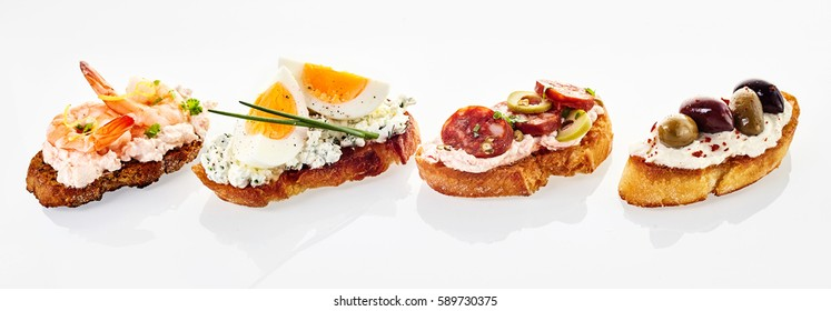 Selection of fresh canapes in a header or banner format with assorted toppings including prawn, egg and chive, chorizo sausage and olives with red pepper on quark cheese on white with reflections
