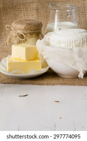 Selection of fresh dairy products - milk, cheese, cottage cheese, yogurt, butter, white wood background