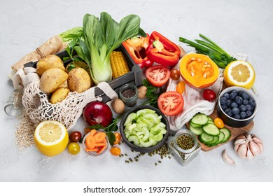 Selection of fresh raw vegetables, fruits and beans on light gray background. Organic food concept.