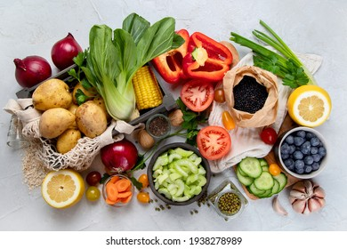 Selection of fresh raw vegetables, fruits and beans on light gray background. Organic food concept. Top view
