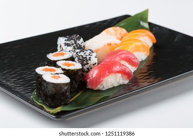 Selection of fresh sushi and sashimi with raw salmon and tuna, nori seaweed and rice served on a leaf on a black platter for a restaurant menu