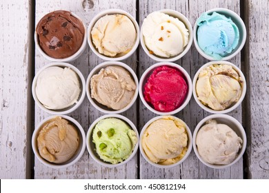 Selection of gourmet flavours of Italian ice cream in vibrant colors served in individual porcelain cups on an old rustic wooden table in an ice cream parlor, overhead view