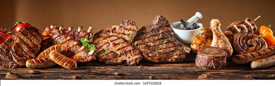 Eine Auswahl an gegrilltem Feinschmeckerfleisch auf rustikalem Holzbrett.