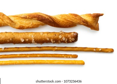 Selection of grissini, pretzels and cheese sticks on white from above.