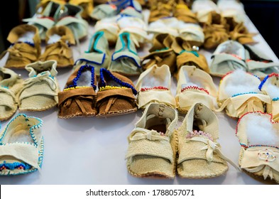 Selection of handmade kids and baby beaded leather Native American Indian moccasins on display for sale at a powwow in San Francisco