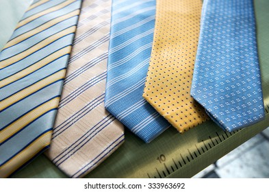 Selection of handmade ties, or neckties, in blue and yellow in different fabrics displayed at a tailor, close up view