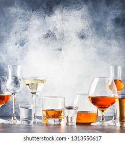 Selection of hard strong alcoholic drinks in big glasses and small shot glass in assortent: vodka, cognac, tequila, brandy and whiskey, grappa, liqueur, vermouth, tincture, rum. Gray bar counter backg