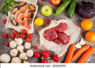 Selection of healthy dietary food products - raw beef, seafood, vegetables, fruits and greens. On a concrete gray table, top view