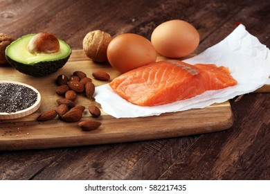 Selection of healthy fat sources, rustic background. Healthy eating, diet concept with salomon and avocado