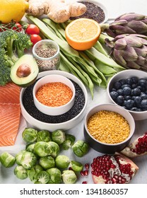 Selection of healthy food. Clean eating concept. Cooking ingredients with fish, superfood, vegetables,  artichokes, brussel sprouts, fruits, legumes  and blueberries
