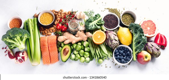 Selection of healthy food. Clean eating concept. Cooking ingredients with fish, superfood, vegetables,  artichokes, brussel sprouts, fruits, legumes  and blueberries. Panorama, banner. Top view