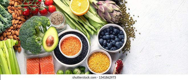 Selection of healthy food. Clean eating concept. Cooking ingredients with fish, superfood, vegetables,  artichokes, brussel sprouts, fruits, legumes  and blueberries. Panorama, banner with copy space