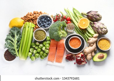 Selection of healthy food. Clean eating concept. Cooking ingredients with fish, superfood, vegetables,  artichokes, brussel sprouts, fruits, legumes  and blueberries. Top view