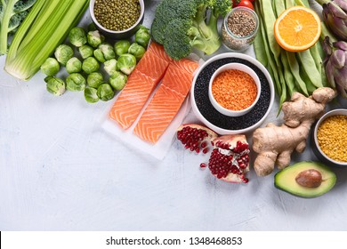 Selection of healthy food. Clean eating concept. Cooking ingredients with fish, superfood, vegetables,  artichokes, brussel sprouts, fruits, legumes  and blueberries. Top view with copy space
