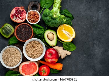 Selection of healthy food: fruits, seeds, cereals, superfoods, vegetables, leafy vegetables on a stone background. Healthy food for humans. Copy space for your text.