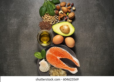 Selection of healthy food. Raw steak of salmon with fresh ingredients on gray background.