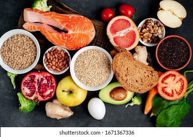Selection of healthy food: salmon, fruits, seeds, cereals, superfoods, vegetables, leafy vegetables on a stone background. Healthy food for people.