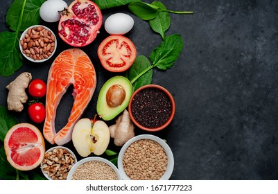 Selection of healthy food: salmon, fruits, seeds, cereals, superfoods, vegetables, leafy vegetables on a stone background  with copy space for your text. Healthy food for people.