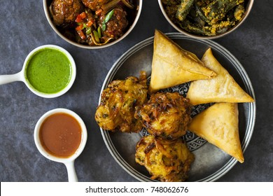 Selection of Indian dishes: samosas, onion bhaji, manchurian balls and  okra