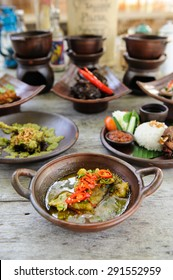 A selection of Indonesian dishes including nasi campur, fish curry and fried chicken with green chili sambal.