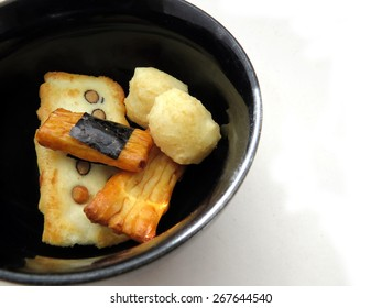 Selection of Japanese rice crackers in a black bowl with white space