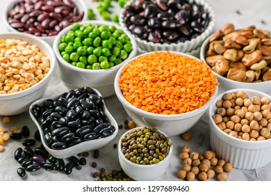 Selection of legumes - beans, lentils, mung, chickpea, pea in white bowls on stone background