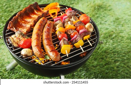 Selection of meat grilling over the coals on a portable barbecue with spicy sausages, beef kebabs and racks of ribs, outdoors on green grass with copyspace