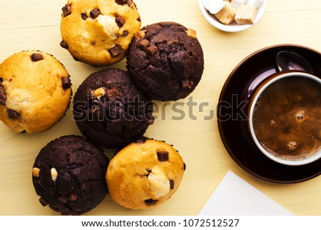 A selection of muffins and coffee on yellow work surface, shot top down