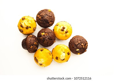 A selection of muffins on white surface shot top down