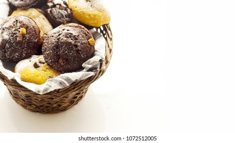 A selection of muffins in wicker basket on white work surface, shot at angle and tight crop for ad space