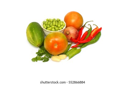 A selection of natural vegetable arranged in and around a Coriander leaves, chilli,beens,onion,garlic,tomato.
