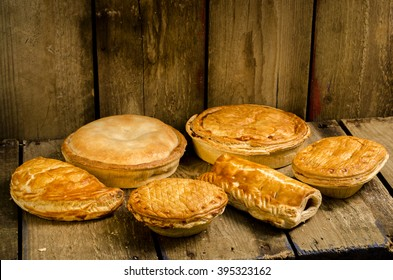 Selection of Pies, Pasties and sausage rolls on a wooden background.