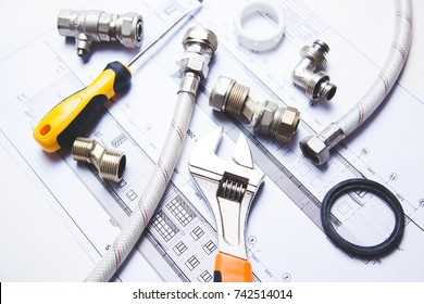 A selection of plumbing tools and fittings on domestic house plans
