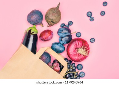 Selection of purple foods - fruits, berries and vegetables in a grocery craft bag on pink background. Purple or eat by color diet concept. Copy space