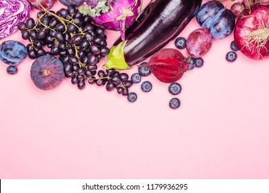 Selection of purple foods - fruits, berries and vegetables on pink background. Purple or eat by color diet concept. Copy space