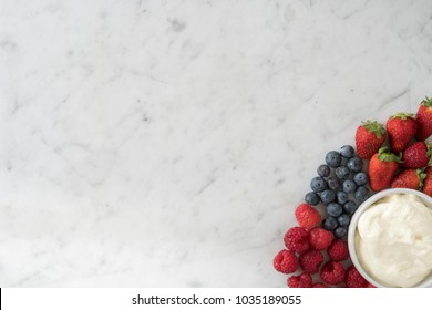 Selection of Raspberries, Strawberries, Blueberries and Cream on Marble Table Top from Above with Copy Space