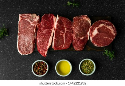 Selection of raw beef meat food steaks against black stone background. New york striploin steak, top blade, rib eye, and other cuts of meat.
