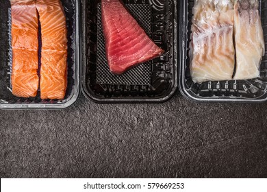 Selection of raw colorful fish fillets : salmon, tuna and codfish in plastic boxes on dark rustic background, top view, border, place for text. Healthy Seafood concept