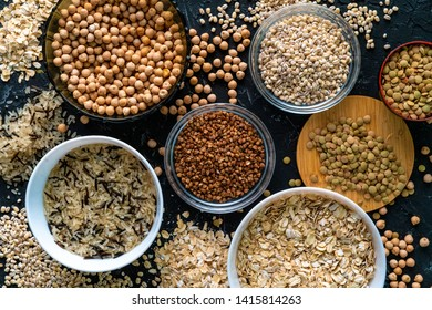 selection of raw uncooked cereals grains  in bulbs with chickpeas oat lentil rice buckwheats
