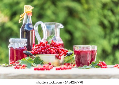 A selection of redcurrant products - marmalade jam syrup must and red vine on table in garden.