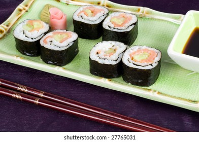 A selection of rolls sushi against a magenta background