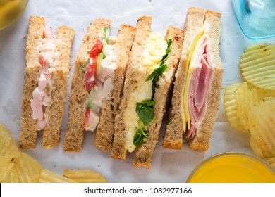 Selection of sandwiches on malted brown bread. Prawns with mayonnaise. Roast chicken breast, vine tomatoes, cucumber, mayonnaise. Egg mayonnaise  and watercress. Ham and cheddar cheese on mayo.