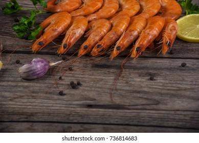 Selection of shrimps for dinner on wooden plate. Food background