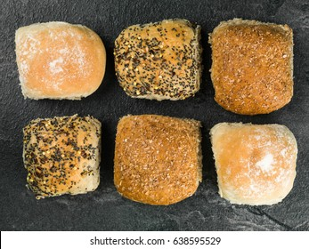 Selection of Six Mixed Bread Rolls or Buns Against a Black Background
