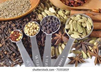 Selection of spice seeds in measuring spoons with a variety of seeds in the background