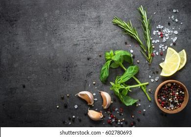 Sélection d'herbes épices et de verdure. Ingrédients pour la cuisine. Arrière-plan cuisine sur table en ardoise noire. Espace de copie de la vue supérieure.